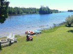 The spectacular view of the lake from the front deck showing kayaks, paddle boat and fire-pit.