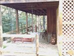 lower porch in back of cabin with swing