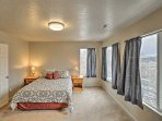 Three picture windows line this queen master bedroom.