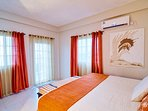 The Orange Sunset room with its kingsize bed and AC unit, opens out to its own private balcony.