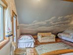 This large bedroom includes a full-sized bed, 2 twin beds, and a futon.
