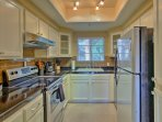 The kitchen is fully equipped with stainless steel appliances and expansive granite counters.