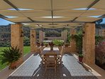 The back side dining area with a shaded pergola