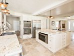 Refrigerator with ice maker, microwave, full-size double oven, stove and dishwasher.