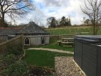 Upper barn garden area with hot tub, dinning area, BBQ & Well House in background