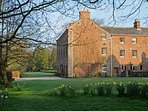 Melmerby Hall in the early springtime with daffodils under the beech trees