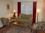 Comfy cozy front room that's huge! Plenty of light & seating. Plish green sofa bed