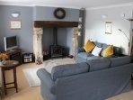 Lounge dining room comfy sofas around inglenook fireplace