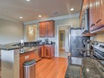 The fully equipped kitchen showcases stainless steel appliances and granite countertops.