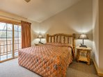 Enjoy restful slumbers in this first bedroom housing a king bed and  balcony access.
