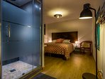 Een grote slaapkamer op de bovenverdieping met douche en grote wastafel. Airconditioning.