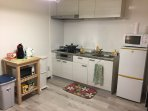 spacious new kitchen with all cooling tools and dishes, microwave, toaster, hot water pot