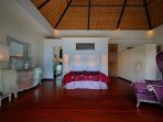 Spacious bedroom with wooden flooring and thatched roof