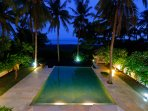 Warmly lit swimming pool with direct access to the beach