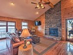 The well-appointed living space is highlighted by a floor-to-ceiling stone fireplace.