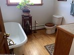 Bathroom with claw foot soaking tub.