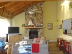 Vaulted ceiling, large rock fireplace and flat screen tv, bay window.