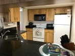 Granite counters, full size kitchen with dishwasher, microwave, toaster oven, fridge, and oven/stove