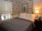 Bedroom with queen bed on main floor with adjoining bathroom