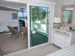 Lower unit: 2nd level: Bedroom with queen bed with access to shared balcony (Partial ocean views)