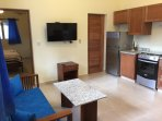 This a the kitchen and living room in a one bedroom unit. There is a table and tv in this are also.