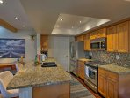 The fully equipped kitchen boasts state-of-the-art appliances and granite countertops.
