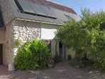 Gite entrance with solar panels, fruiting peach tree and cannas by the door