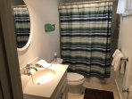 Fully renovated basement bathroom with tub and shower.