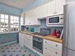 Very well equipped kitchen overlooks garden and sea