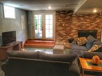 Basement den with TV, fireplace, Futon, and game table
