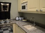 Small kitchen equipped with electric hob, oven, fridge/freezer, and washing machine