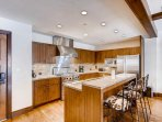 The well-crafted Kitchen island serves as a breakfast bar and gathering point.