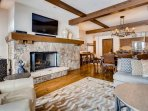 The living area's warm mountain decor and exposed wood beams make for a perfect evening around the fire with family and...