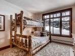 The hearty quilts and natural wood bunk beds add to the idyllic mountain scenery out the window.