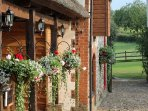 The essence of Red Doors Farm with cascading hanging baskets & views to the surrounding countryside.