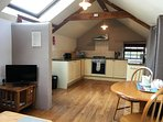 Open-plan to kitchen. Vaulted ceiling with exposed oak beams throughout