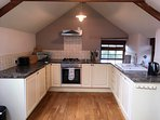 Spacious kitchen equipped with fridge, freezer, dishwasher, electric oven, gas hob and microwave