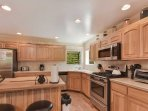 The kitchen features stainless steel appliances and an island with bar seating.