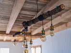 Le lustre de la salle à manger, sous le plafond en vieux bois.
