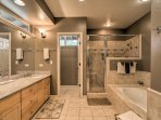 Designed to impress, this en-suite bathroom hosts a built-in tub, double vanities, and a walk-in shower.
