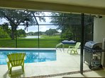 Screened patio with pool, grill and outside dining set with view of lake