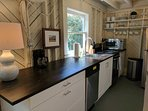 Galley kitchen with stove, oven, microwave, dishwasher, refrigerator, toaster + coffee maker.