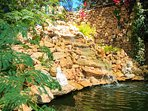 Stone waterfall landscaped by us.  You will never want to leave !