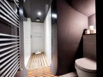 The contemporary bathroom benefits from a walk-in rain shower and wooden...