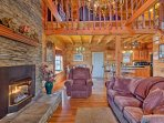 Hardwood floors, a stone gas fireplace, and vaulted ceilings embellish the rustic living room.