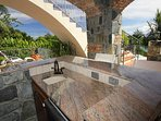 The pool desk has a beautiful granite, stone and mahogany bar