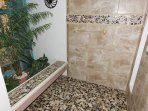 "The garden shower has a ""zen like"" feel to it with the sand colored tiles and inlaid stones."