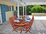 The teak exterior table is surrounded by a spacious coral stone deck
