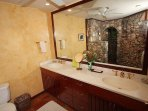 This view of the 2nd master bath shows the stone shower reflected in the mirror