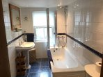 A bright family bathroom provides opportunity for a long soak, or a good, hot shower for busier days